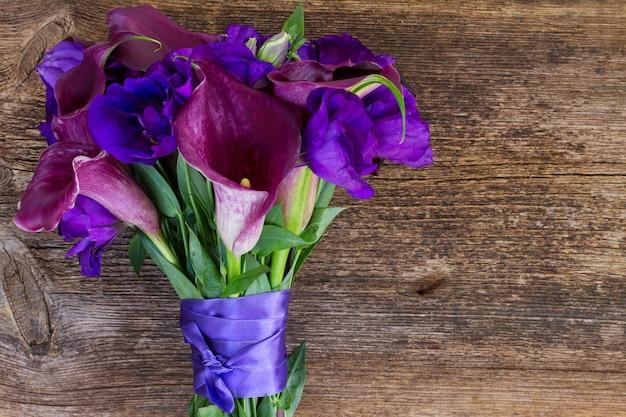 Boeket verse calla lelie en eustoma bloemen op houten tafel