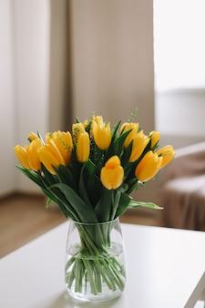 Boeket verse gele tulpen op een tafel in het interieur van de woonkamer