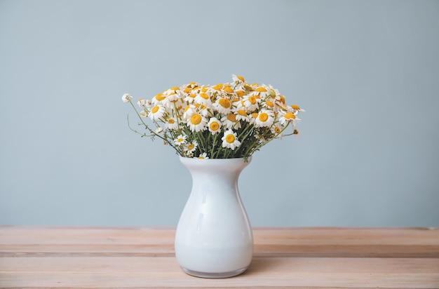 Boeket verse kamille bloemen in vaas op tafel tegen een grijze achtergrond