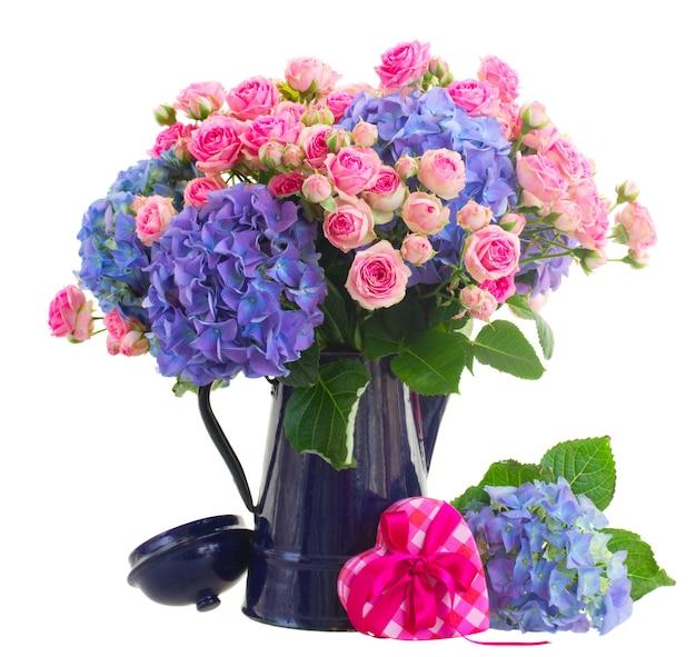 Boeket verse roze rozen en blauwe hortenzia bloemen in blauwe pot geïsoleerd op witte ruimte