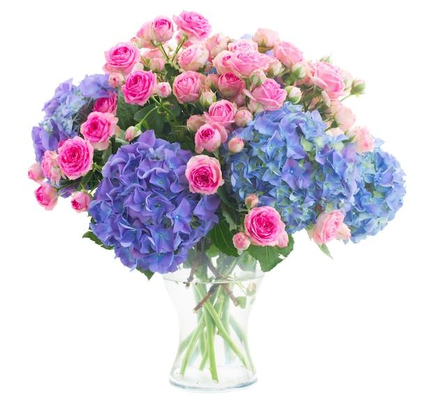Boeket verse roze rozen en blauwe hortenzia bloemen in glasvaas geïsoleerd op witte ruimte