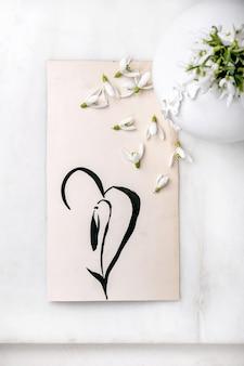 Boeket verse sneeuwklokjes lentebloemen in witte porseleinen vaas met slakkenhuis en met de hand getekende sneeuwklokje op wit marmeren tafel. samenstelling lente