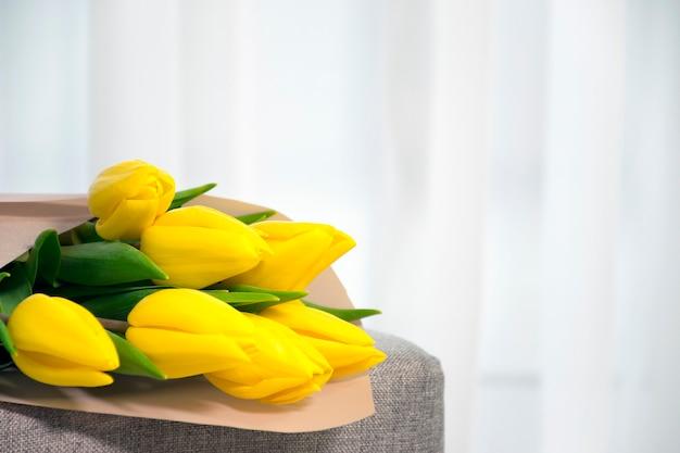 Boeket verse tulpen gele kleur op grijze fauteuil in de buurt van tulled raam in interieur