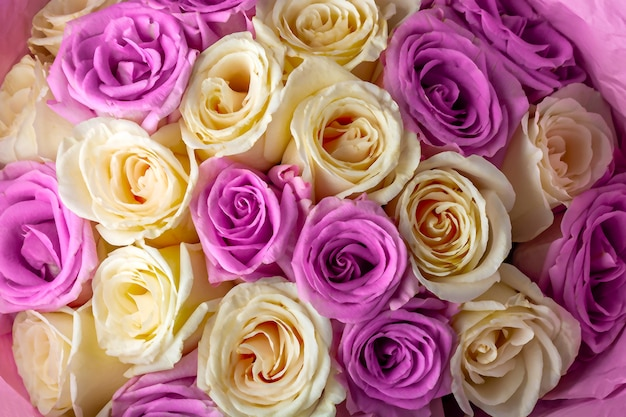 Boeket verse verbazingwekkende witte en paarse rozen in ambachtelijke papier