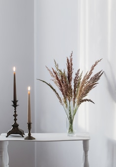 Boeket wilde bloemen en brandende kaarsen in zonlicht in wit interieur