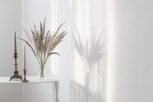 Boeket wilde bloemen en kaarsen in zonlicht in wit interieur