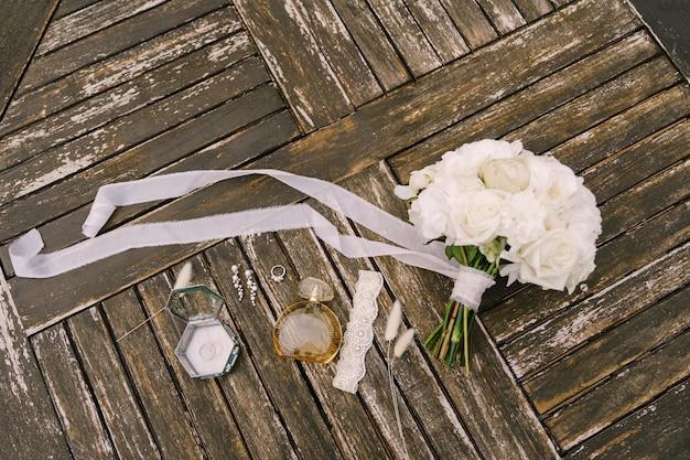 Boeket witte rozen met een lang ontwikkellint voor de bruid met kouseband parfumflesje