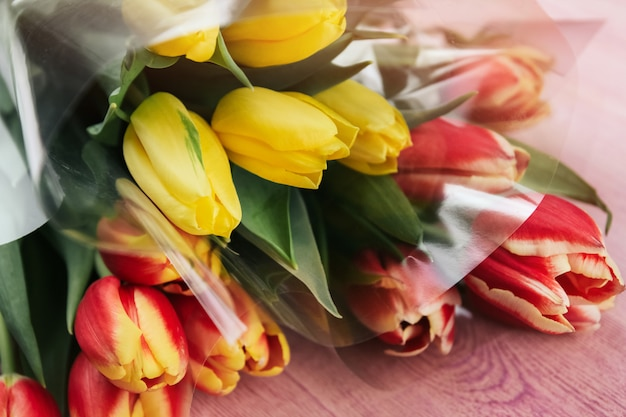 Boeketten van gele en rode tulpen op een roze houten oppervlak