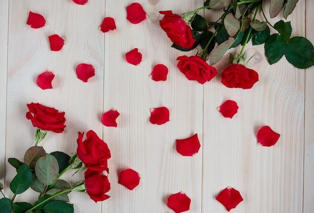 Boeketten van rode rozen, rozenblaadjes op een lichte houten achtergrond