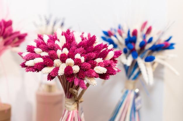 Boeketten van roze en blauwe wilde gedroogde gestabiliseerde bloemen in de winkel. floristische samenstelling