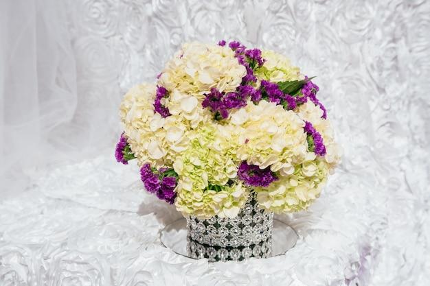 Boeketten van rozen op een feestelijke huwelijkslijst in de bloemen van het restauranthuwelijk en een lijst