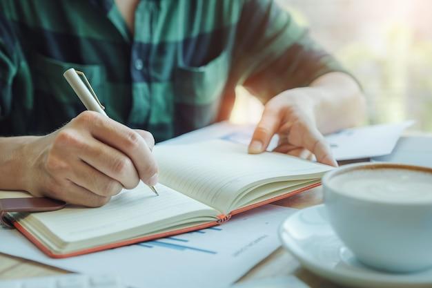 Boekhouder concept. de accountant die pen gebruikt om gegevens te noteren voor controle van de juistheid van het investeringsbudget met behulp van computerlaptop en documentgegevens voor analyse.