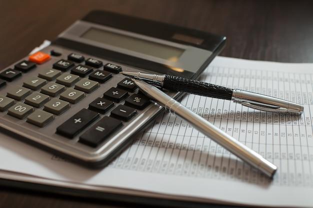 Boekhoudkundige documenten, pennen en rekenmachine close-up