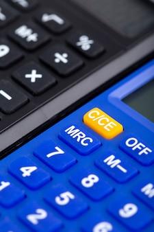 Boekhoudkundige rekenmachines handgebruik zwart en blauw bedrijf van dichtbij