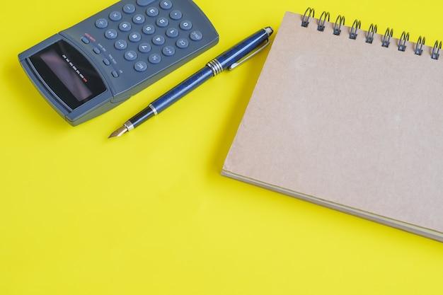 Boeknota en calculator op kleurenachtergrond.