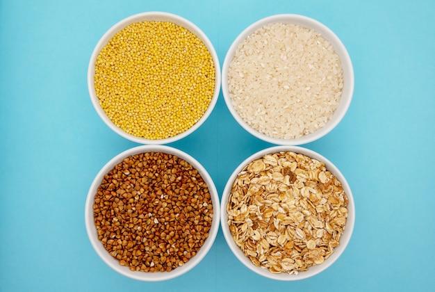 Boekweit, gierst, rijst en tarwe op blauwe achtergrond