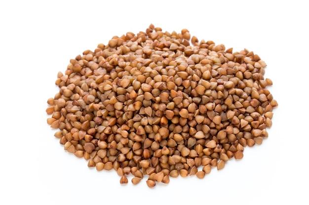 Boekweit graankorrels geïsoleerd op het witte oppervlak.