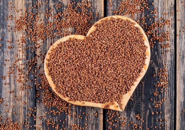 Boekweit in een hartvormige snijplank op een donkere houten. bovenaanzicht.