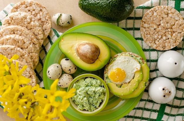 Boekweit knäckebröd met cottage cheese, spinazie, avocado en gebakken kwarteleitjes