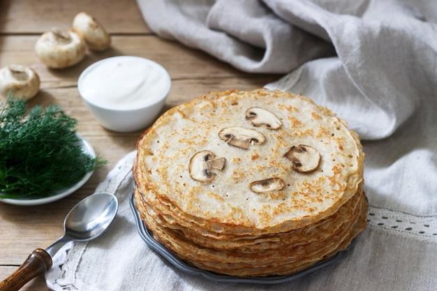 Boekweit pannenkoeken geserveerd met zure room en dille op een houten tafel. rustieke stijl.
