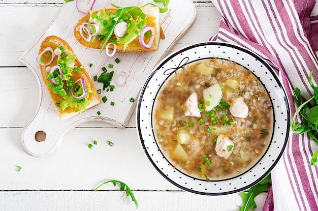 Boekweit soep met kip in een plaat, brood met mosterd ang rode ui op een houten witte tafel. bovenaanzicht