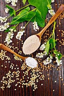 Boekweitmeel van bruine en groene granen in twee lepels, bloemen en bladeren op de achtergrond van een donkere houten plank van bovenaf