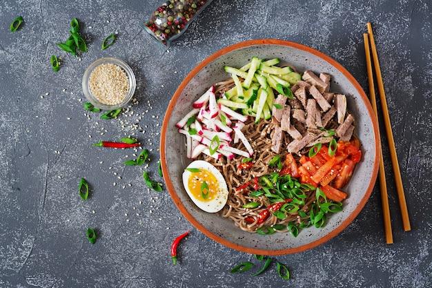 Boekweitnoedels met rundvlees, eieren en groenten. koreaans eten. boekweitpastasoep. bovenaanzicht plat leggen