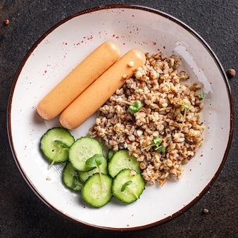 Boekweitpap en worstjes verse salade komkommer klaar om maaltijdsnack op tafel te eten