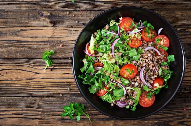 Boekweitsalade met kerstomaatjes, rode ui en verse kruiden. veganistisch eten. dieet menu. bovenaanzicht plat leggen
