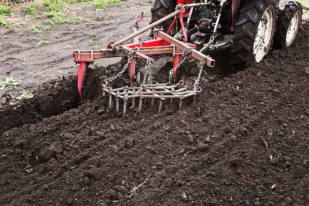 Boer bereidt land voor om te zaaien. trekker aan het werk op de boerderij, een modern landbouwtransport, werken in het veld, vruchtbare grond, grondbewerking, landbouwmachine, kopieerruimte, kopieerruimte.