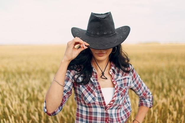 Boer draagt cowboyhoed, plaidoverhemd en spijkerbroek op een tarweveld