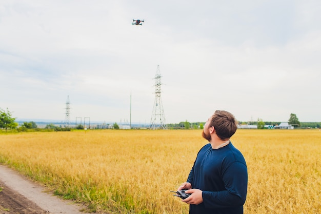 Boer houdt afstandsbediening met zijn handen terwijl quadcopter op de achtergrond vliegt. drone zweeft achter de agronoom in een tarweveld. nieuwe technologieën en innovaties in de landbouw. achteraanzicht