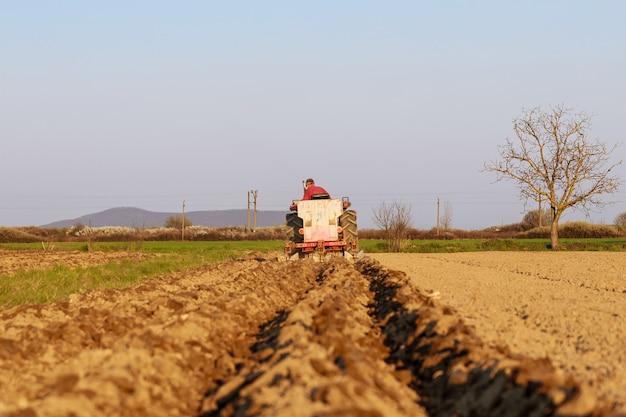 Boer in een blauwe tractor die aardappelen plant met een kleine tractor