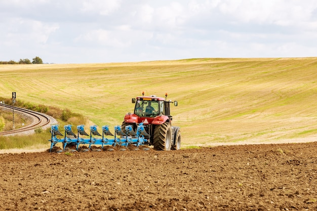 Boer in een grote rode tractor land met ploeg voorbereiden om te zaaien