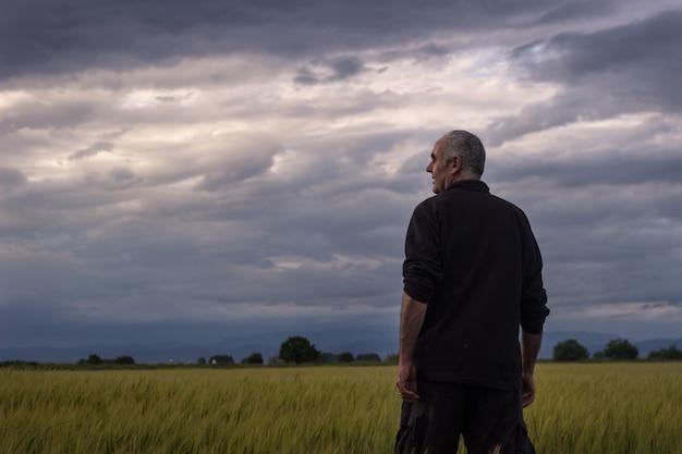 Boer in een storm dag kijken naar de oogst