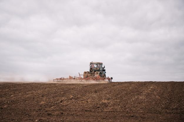 Boer in trekker land met zaaibed cultivator in landbouwgronden voorbereiden. trekker ploegt een veld. agrarisch werk in verwerking, landteelt. boeren bereiden land voor en bemesten. agrarisch
