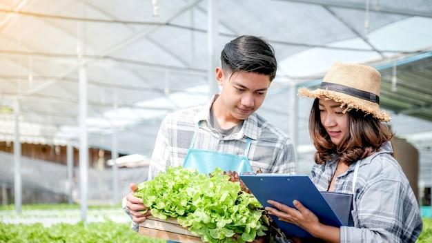 Boer inspecteert kwaliteit van plantaardige biologische salade en sla van hydrocultuurboerderij en maakt aantekeningen