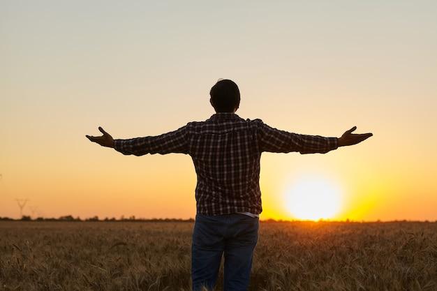 Boer, jonge knappe boer die in een tarweveld staat en uitkijkt naar de zonsondergang, hief zijn handen op naar de zon