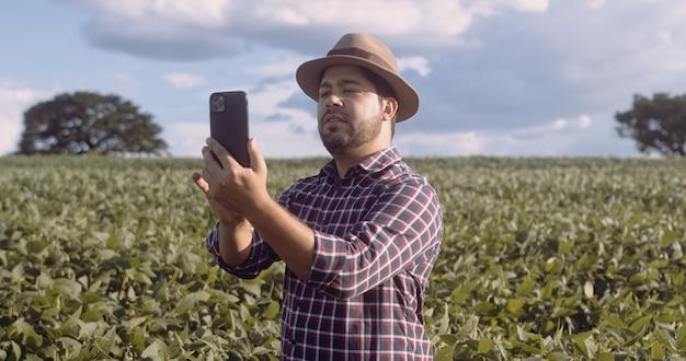 Boer maakt foto's van sojaplantages. kwaliteitscontrole. het werk van een landbouwkundige. braziliaanse boerderij.