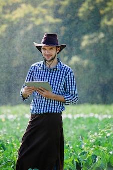 Boer man agronoom zon werknemer controle digitale tablet computer plantage technologie hoed sprinkler systeem water
