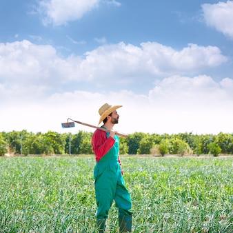 Boer man met schoffel kijken naar zijn veld