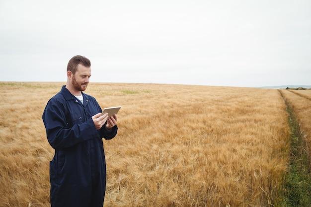 Boer met behulp van digitale tablet in het veld