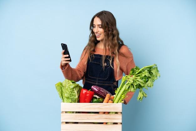 Boer met vers geplukte groenten in een doos die een selfie maakt