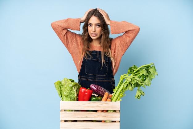 Boer met vers geplukte groenten in een doos gefrustreerd en neemt de handen op het hoofd