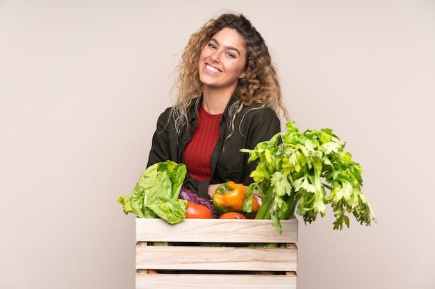 Boer met vers geplukte groenten in een doos geïsoleerd op beige muur lachen
