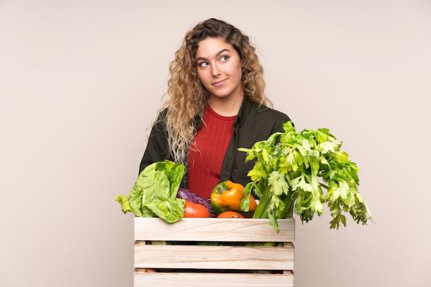 Boer met vers geplukte groenten in een doos geïsoleerd op beige muur staan en op zoek naar de kant
