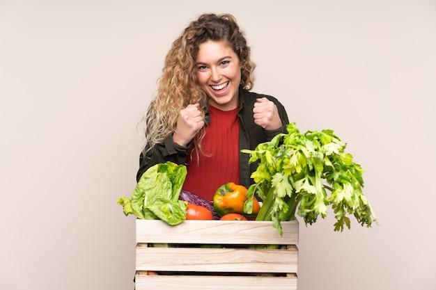 Boer met vers geplukte groenten in een doos geïsoleerd op beige muur vieren een overwinning