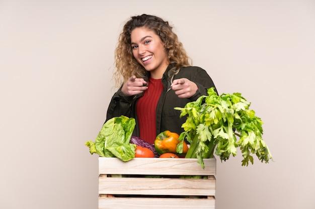 Boer met vers geplukte groenten in een doos geïsoleerd op beige muur wijst vinger naar je