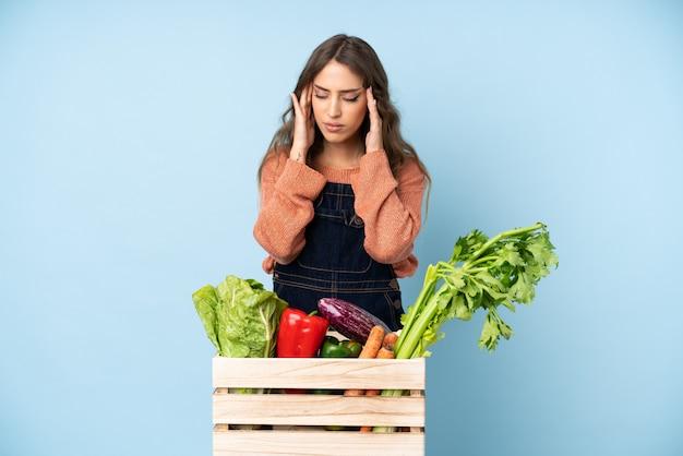 Boer met vers geplukte groenten in een doos met hoofdpijn