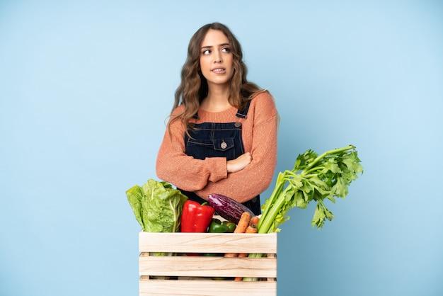 Boer met vers geplukte groenten in een doos met verwarde gezichtsuitdrukking
